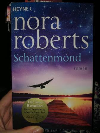 blaues Buch, Schattenmond von Nora Roberts, Steg an einem See mit fliegendem Vogel davor