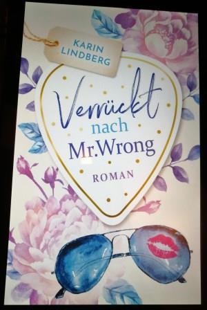 """Buchcover """"Verrückt nach Mr. Wrong"""" von Karin Lindberg. Pastellfarbenes Cover mit Sonnenbrille, Blumen und dem Titel in einem Herzen."""