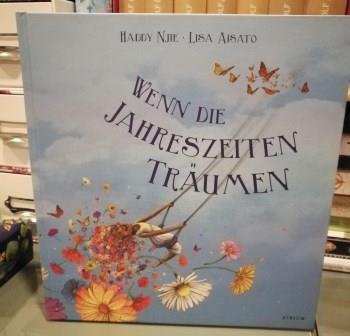 """Buchcover vom Buch """"Wenn die Jahreszeiten träumen"""". Hellblaub mit blumen und schaukelndem Kind"""