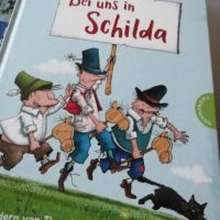 """Kinderbuch """"Bei uns in Schilda"""" von Otfried Preußler. 3 Schildbürger halten ein Schild mit dem Buchtitel hoch und rennen einer schwarzen Katze nach"""