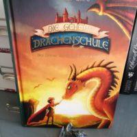 Buch mit kleinem Drachen davor, auf dem Buch ist ein Junge und ein Drache zu sehen