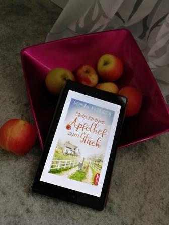 """eine Schale Äpfel und ein Reader mit dem Cover von """"Mein kleiner Apfelhof zum Glück"""" von Sonja Flieder"""