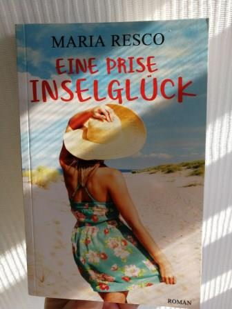 Buchcover im Sonnenlicht mit Frau auf dem Cover. Titel: Eine Prise Inselglück von Maria Resco